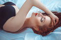 Sensual red hair woman lying in bed woma studio Royalty Free Stock Photography
