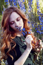Sensual redheaded woman in sunset light smelling flowers blue Royalty Free Stock Images