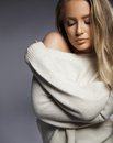 Sensual sexy model in oversized sweater blond woman posing and a white portrait shot on grey background winter clothes Stock Image