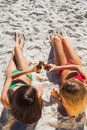 Sensual tanned blonde and brunette having beers on the beach Stock Photos