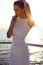 Sensual woman with blond hair in elegant white dress posing on yacht fashion outdoor photo of beautiful Royalty Free Stock Images