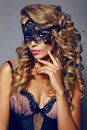 Sensual woman with luxurios blond hair with mask on face