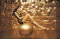 Sensual woman playing on the big ball gold Royalty Free Stock Photos