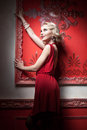 Sensual woman in red dress vintage room rich interior Stock Photo