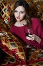 Sensual woman with a red wine glass on a magnificent sofa Royalty Free Stock Photo