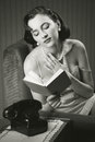 Sensual woman wearing lingerie reading book armchair Stock Photo