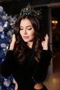 Sensual woman wears elegant dress, posing beside decorated Christmas tree Royalty Free Stock Photo