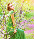 Sensual wood nymph enjoying spring nature sitting in blooming garden with closed eyes dreamy girl in long green dress natural Stock Photography