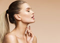 Sensual young girl in profile touching her clean skin. Royalty Free Stock Photo