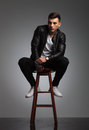Sensual young man posing seated on stool in studio Royalty Free Stock Photo