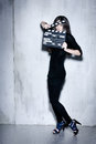 Sensuality beautiful woman with long hairholding clapperboard hair dressed in black posing in studio holding Royalty Free Stock Photos