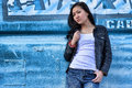 Sensuality woman in white t shirt black leather jacket blue jeans and black long hair in the background blue urban iron photo Stock Photography