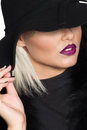 Sensuous chic blond woman in black high angle view of a gorgeous a wide brimmed hat concealing her eyes but revealing her parted Stock Photos