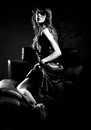 Sensuous woman on leather seat side view of a young against dark background Stock Photography