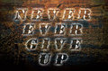 Sentence Never ever give up written on nature wooden background. Royalty Free Stock Photo