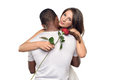 Sentimental young woman hugging her boyfriend women or sweetheart as she smiles tenderly down at a single red rose he has just Stock Image