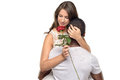 Sentimental young woman hugging her boyfriend women or sweetheart as she smiles tenderly down at a single red rose he has just Royalty Free Stock Images