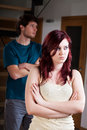 Separate lovers with problems a men and a women standing separately theris arms crossed and sad faces Royalty Free Stock Images