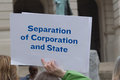 Separation of corporation and state a person holding a protest sign at a capitol against the influence american corporations in Stock Images