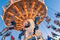 Sept. 2, 2012 - Vancouver, BC: Fun fair riders on whirling retro swing ride, late afternoon at PNE Exhibition. Royalty Free Stock Photo