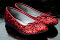 Sequined red slippers on dark tile. Stock Image