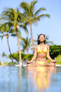 Serene meditating woman relaxing at luxury travel holiday vacation resort happy blissful asian young in bikini in meditation Stock Photo