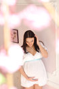 serene pregnant in a white dress on pink  background Royalty Free Stock Photo
