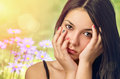 Serene teenager beautiful teenage girl with hands on face over spring flowery background Stock Photo