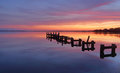 Serene water and stunning sunrise at gorokan jetty australia the old broken Stock Photography