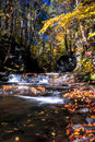 Serene waterfalls flow gently over rocks adorned with Autumn leaves Royalty Free Stock Photo
