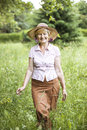 Serenity. Friendly Senior Peasant Woman in Straw in Meadow Smiling Royalty Free Stock Images