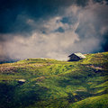 Serenity serene lonely scenery background concept old house in hills in mountins on alpine meadow in clouds vintage style cross Royalty Free Stock Photography