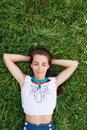 Serenity young woman lying down on grass with eyes closed Stock Photo