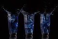 Serial arrangement of blue liquid splashing in glass on black background Royalty Free Stock Photography