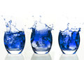 Serial arrangement of blue liquid splashing in tumbler on white background Royalty Free Stock Images