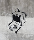 Serial graffiti tv eating a human brain black paint on a grey wall Royalty Free Stock Photography