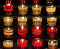 Series of votive candles lit placed inside small glasses of colored glass of red and yellow Royalty Free Stock Photo