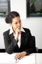 Serious african american businesswoman attractive young in a stylish suit sitting at a table in a meeting listening to a colleague Stock Photography