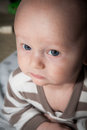 Serious baby with blue eyes and annoyed or expression up close on stomach playing Royalty Free Stock Photography