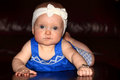 Serious baby a girl wearing a bracelet and headband laying on her tummy shallow depth of field dark background Royalty Free Stock Photo