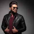 Serious bad boy wearing in jacket and sunglasses looking away leather to his side on gray background Stock Photos