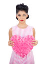 Serious black hair model holding a pink heart shaped pillow Royalty Free Stock Photo