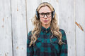 Serious blonde listening music with headphones against bleached wooden planks Royalty Free Stock Photos