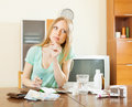 Serious blonde woman with medications and money at table in living room Stock Photography