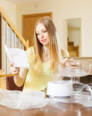 Serious blonde woman reading user manual for new electric steamer at home Stock Photos