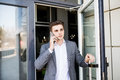 Serious business man in suit talking on phone in office and leaving the office building Royalty Free Stock Photo