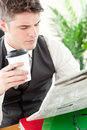 Serious businessman drinking coffee reading news Stock Images