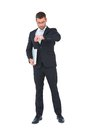 Serious businessman holding laptop checking time on white background Stock Images