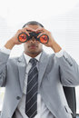 Serious businessman looking through binoculars young in office Stock Image