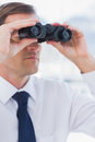 Serious businessman looking at the future with binoculars Stock Photo